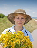 Woman with bunch of flowers. Attractive young woman in countryside with sun hat and bunch of yellow flowers blue sky and field in background Stock Photos
