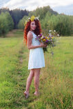 Woman with bunch of flowers on meadow at summer day Royalty Free Stock Photo