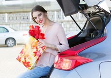 Woman with bunch of tulips near car Stock Photography