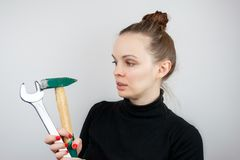 A woman with bunched hair and a black sweater looks at a hammer and a big wrench, while hoding them in her hands.  royalty free stock images