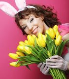 Woman with Bunny Ears holding yellow tulips Royalty Free Stock Images