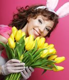 Woman with Bunny Ears holding yellow tulips Royalty Free Stock Image