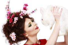 Woman with a bunny, eggs and flowers spring easter concept Stock Photo