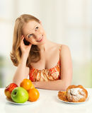 Woman  choose between healthy and unhealthy food Stock Photo