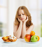 Woman  choose between healthy and unhealthy food Royalty Free Stock Photo