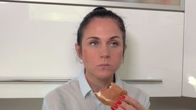 Woman with burger in kitchen. In room stock video footage