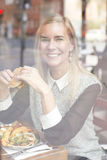 Woman with burger looking through window Royalty Free Stock Photo