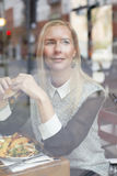 Woman with burger looking through window Royalty Free Stock Photos