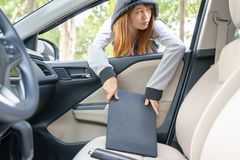 Woman burglar steal a laptop through the window of car - theft c. Oncept royalty free stock image