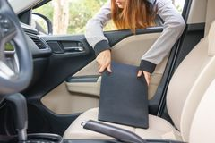 Woman burglar steal a laptop through the window of car - theft c. Oncept stock image