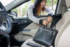 Woman burglar steal a shoulder bag through the window of car - t. Heft concept royalty free stock image