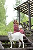 Woman in a burgundy dress on a farm with a goose in her arms and a white goat. Near stock photography