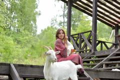 Woman in a burgundy dress on a farm with a goose in her arms and a white goat. Near stock photo