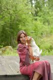 Woman in burgundy dress on a farm with a goose. In her arms stock photos