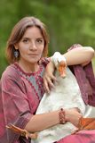 Woman in burgundy dress on a farm with a goose. In her arms royalty free stock images