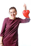 Woman in a burgundy dress who laughs holding heart in her hand Stock Photo