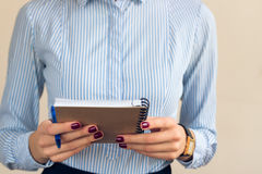 Woman with a burgundy manicure in a blue striped shirt holds notebook Stock Image