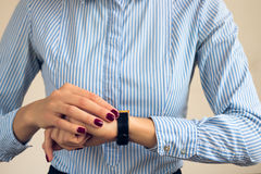 Woman with a burgundy manicure in a blue striped shirt looking the time Stock Photography