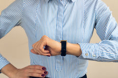 Woman with a burgundy manicure in a blue striped shirt looking the time Stock Photos