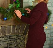 A woman in burgundy stands near the fireplace, which is decorated with Christmas-tree toys royalty free stock photography