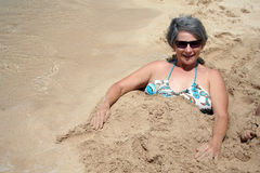 Woman Buried in Sand. A middle-aged woman smiles at the camera after being buried in the sand Stock Images