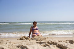 Woman buried in the sand on the beach Stock Images