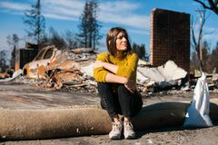 Woman at burned ruined house and yard, after fire disaster. Sad young owner woman sitting in front of burned ruined house and yard, after fire, consequences of royalty free stock photo