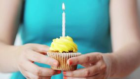 Woman with burning candle on birthday cupcake stock video