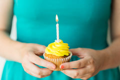 Woman with burning candle on birthday cupcake. Holiday, celebration, people, greeting and party concept - close up of woman with burning candle on birthday Royalty Free Stock Photo