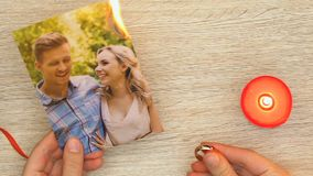 Woman burning family photo and holding engagement ring, divorce and betrayal. Stock footage stock video footage