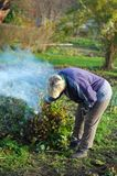 Woman burning the stalks in the garden. Work in the gardenn Royalty Free Stock Image