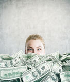 Woman burried in cash in concrete room Royalty Free Stock Photo