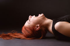 Woman bursts out laughing. Red-haired woman laying on her back on the floor and laughing like mad Stock Photo