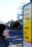 Woman at bus stop. Women looking at bus stop poster stating this bus stop is not in use Royalty Free Stock Photo