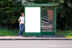 Woman at a bus stop blank billboard. A woman standing at a rural bus stop leaning on a shelter with a blank billboard, clipping path included for you to add your royalty free stock photo
