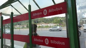 Woman at bus stop in European city, urban passenger transportation service. Stock footage stock video