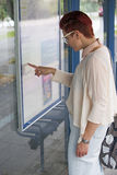 Woman at bus stop looking at timetable Royalty Free Stock Image