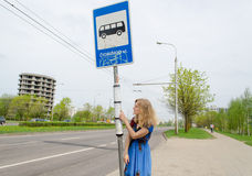 Woman at bus stop with pole tags driving schedules Royalty Free Stock Images