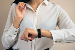 Woman in business attire looking the time on hand watch closeup Royalty Free Stock Images