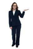 Woman in business attire posing with an open palm Stock Image