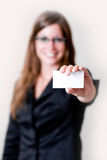 Woman and business card. Modern young business woman holding out business card in air. Focus on business card and hand. Perfect for adding your own copy space Royalty Free Stock Photo