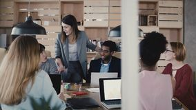 Woman business coach gives directions to team. Young confident European female boss leads multiethnic office meeting 4K. stock video footage