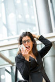 Woman business crisis and stress. Upset businesswoman screaming crazy on phone. Anxious woman on business problems and crisis receiving bad financial news on Stock Photo