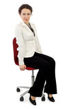 Woman in business dress sitting on red armchair Royalty Free Stock Photography