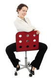 Woman in business dress sitting on red armchair Royalty Free Stock Photos