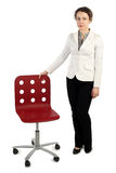Woman in business dress standing near red armchair Stock Photos