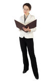 Woman in business dress standing and reading Stock Images