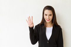 Woman business executive showing 4 or four fingers hand gesture. On plain background with space for text or copy Stock Photo