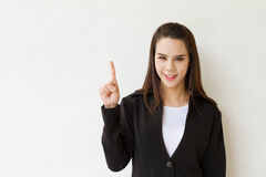 Woman business executive showing 1 or one finger hand gesture. On plain background Royalty Free Stock Image