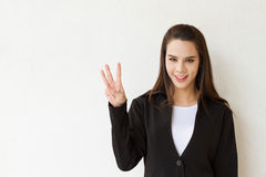 Woman business executive showing 3 or three fingers hand gesture. On plain background with space for text or copy Royalty Free Stock Photos